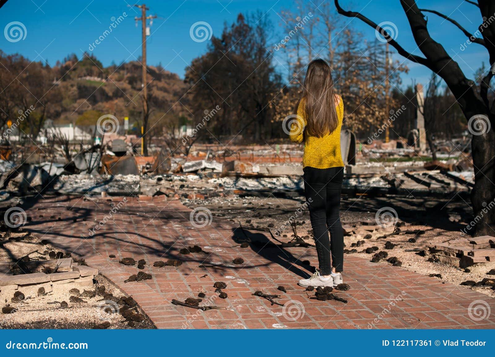 Vrouw die haar gebrand huis na brandramp bekijken