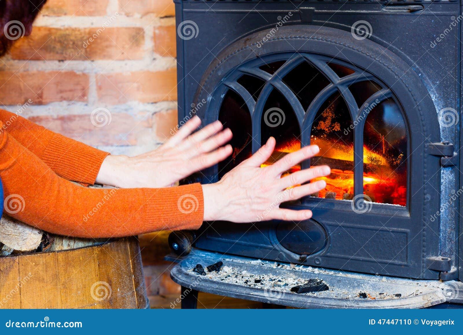 Vrouw die haar handen verwarmen bij het binnenland van de brandopen haard heating