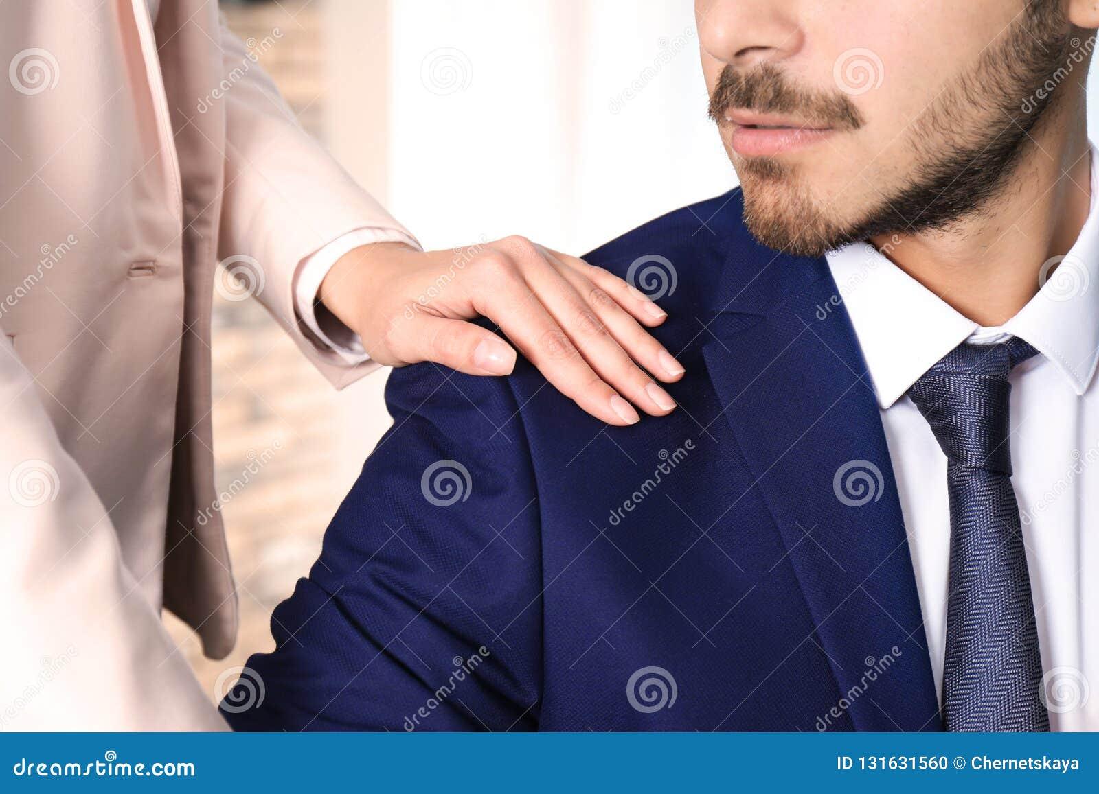 Vrouw die haar mannelijke collega in bureau, close-up lastig vallen