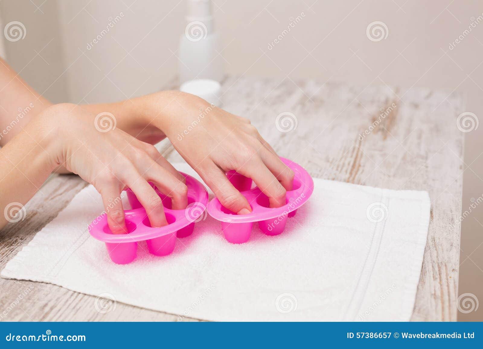 Vrouw die haar spijkers in spijkerkommen doorweken