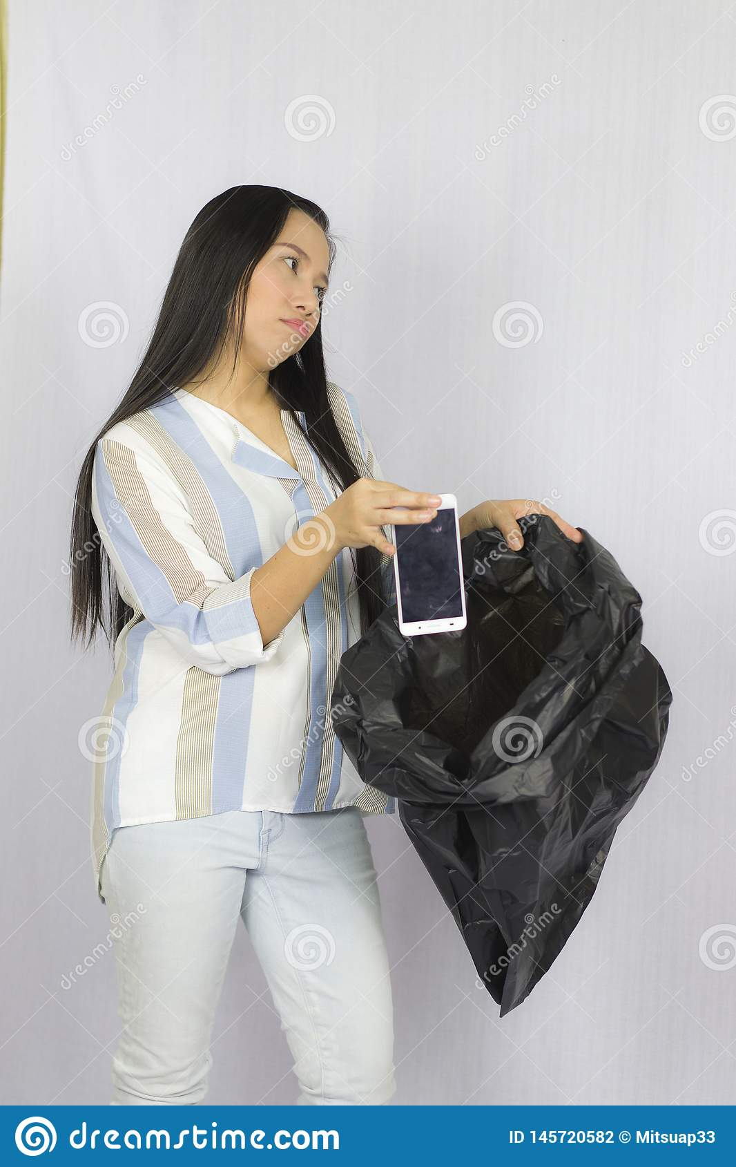 Vrouw die haar telefoon werpen in de vuilniszak, stellen ge?soleerd op grijze achtergrond