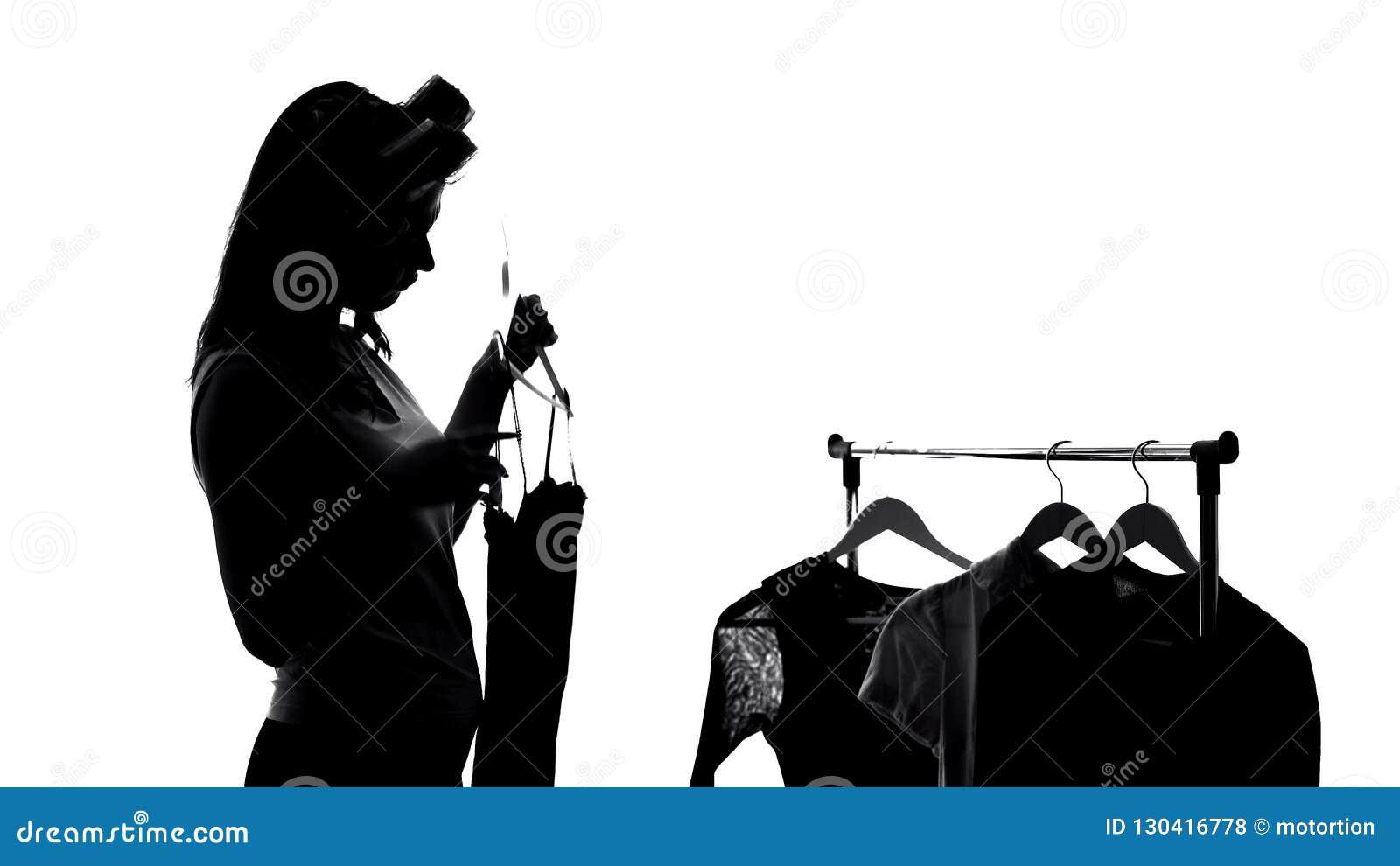 Vrouw die in haarrollen kleding kiezen, die voor vergadering, manierkleren voorbereidingen treffen
