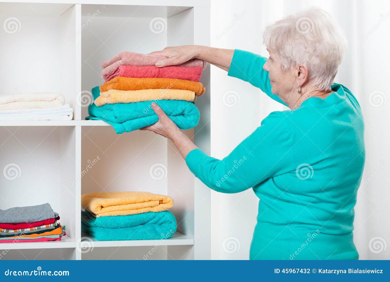 Vrouw die handdoeken zetten aan de plank