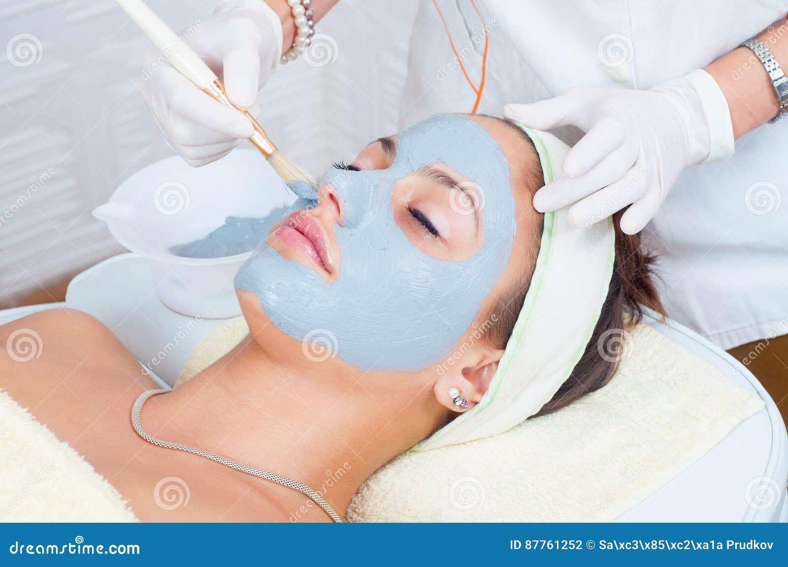 Vrouw die in health spa liggen terwijl het gezichtsmasker op haar gezicht wordt gezet