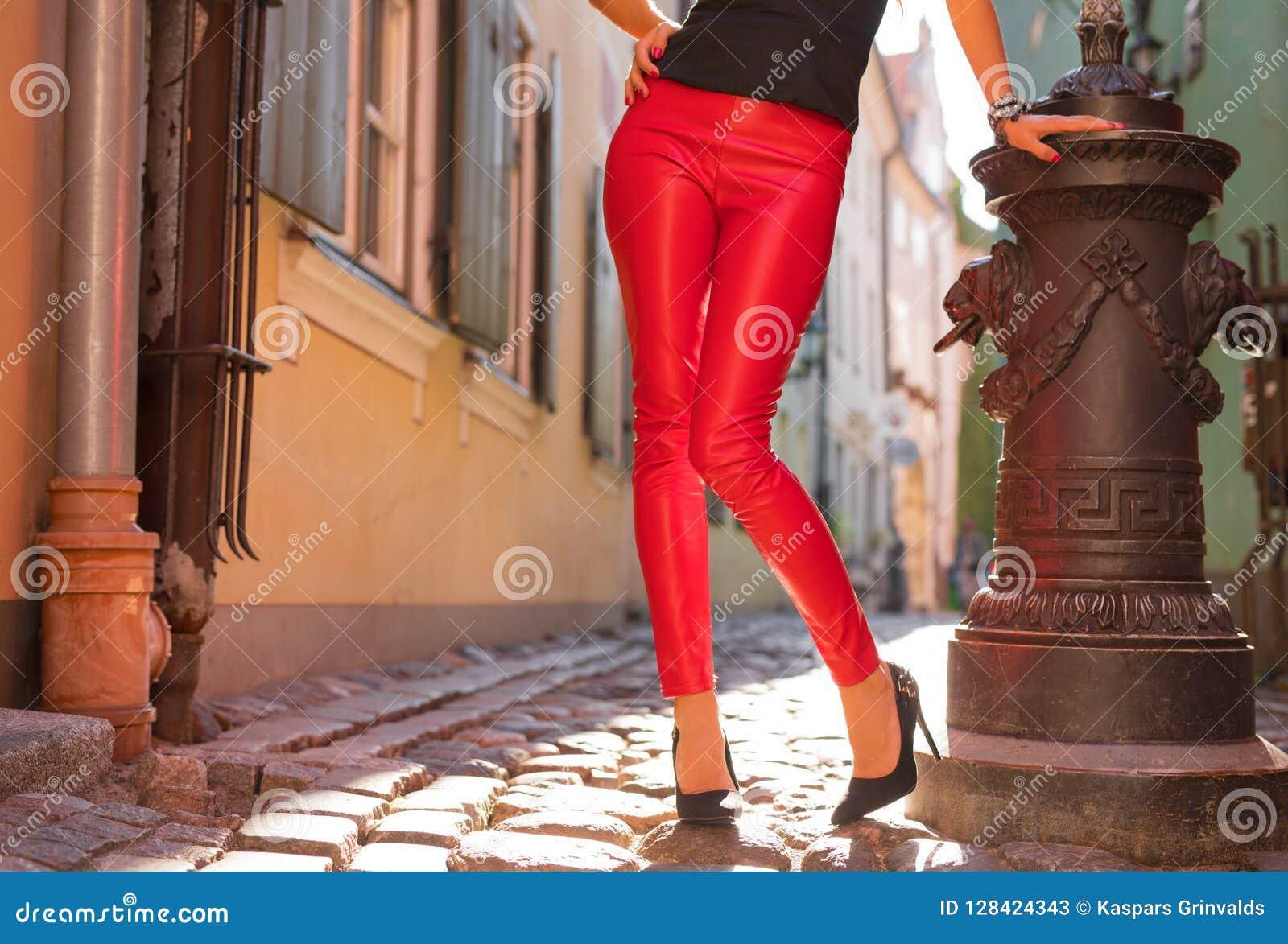 Vrouw die heldere rode leerbroeken en hoge hielen dragen