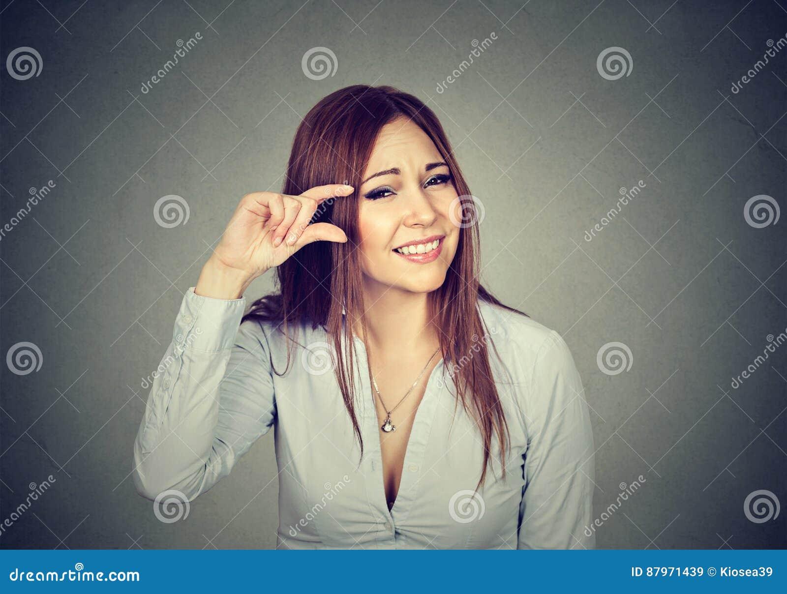 Vrouw die het kleine gebaar van de bedraggrootte met vingers tonen