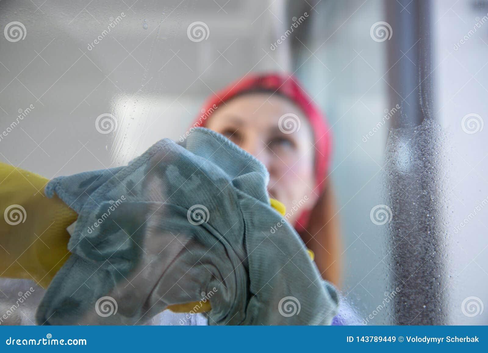 Vrouw die huishoudelijk werk doet Huisvrouw Portrait While Cleaning Foto door het glas