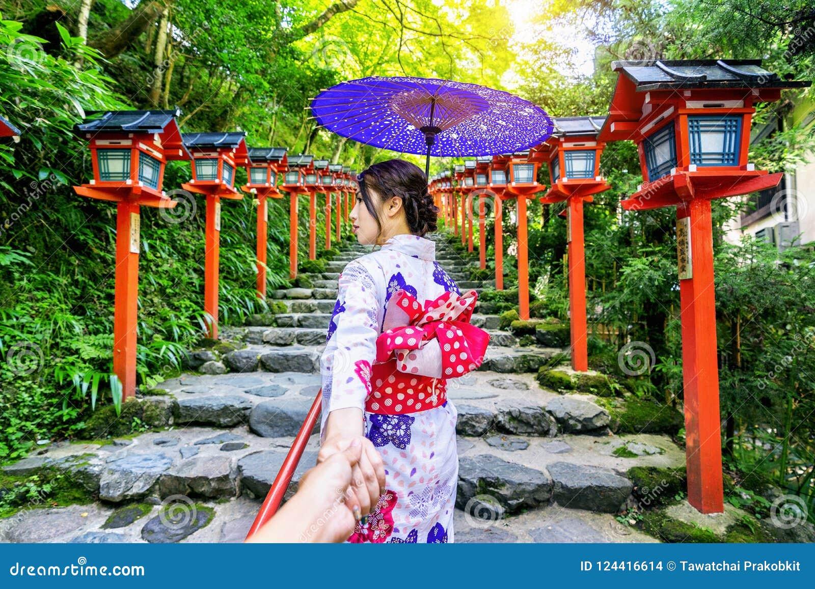 Vrouw die Japanse traditionele de man ` s van de kimonoholding hand dragen en hem leiden tot Kifune-heiligdom, Kyoto in Japan