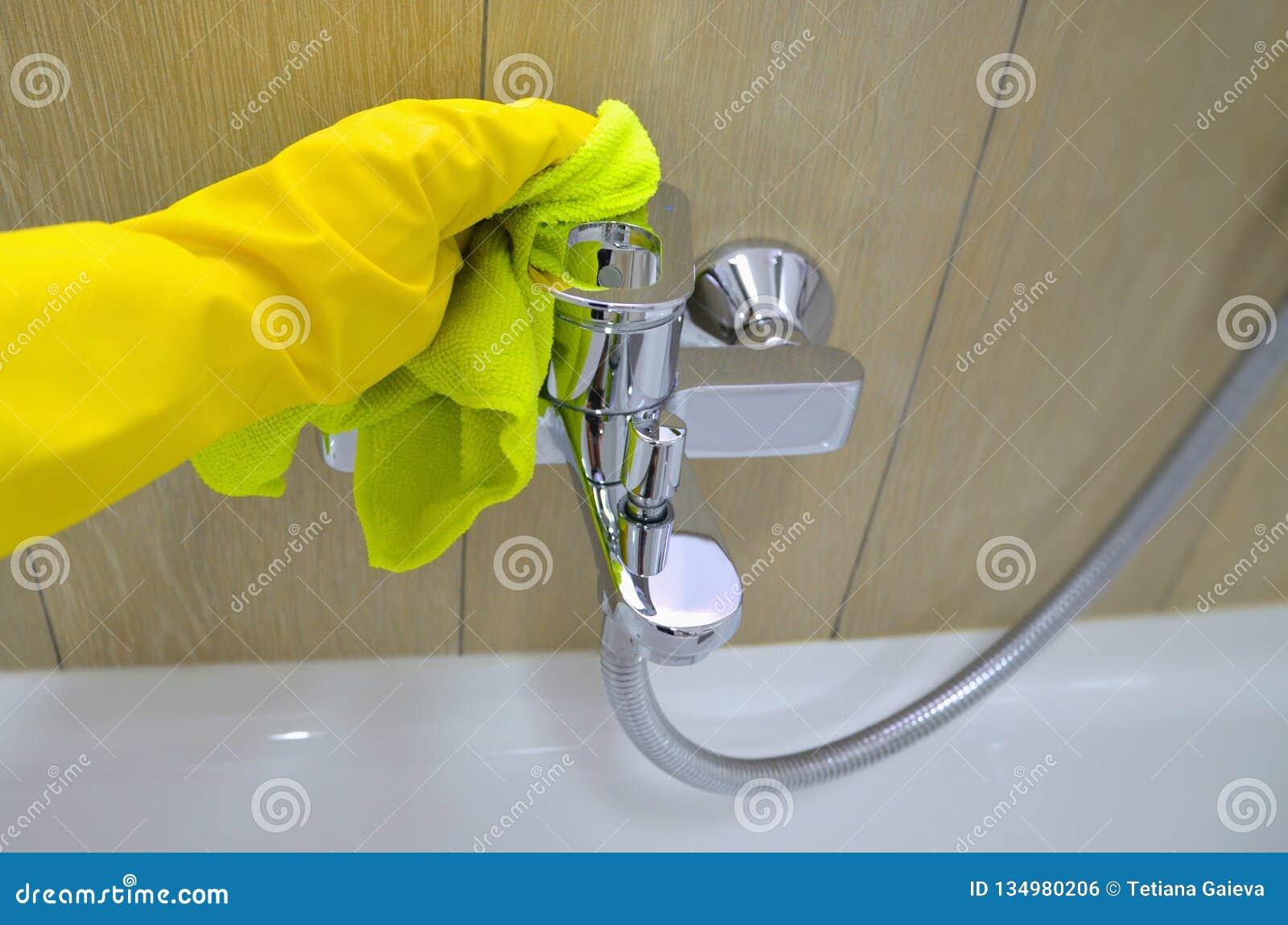 Vrouw die karweien in badkamers doen, het schoonmaken van waterkraan beeld