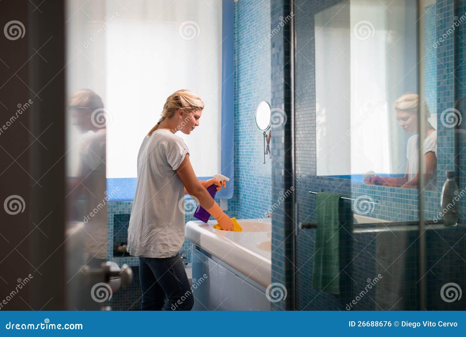 Vrouw die karweien thuis doet en badkamers schoonmaakt
