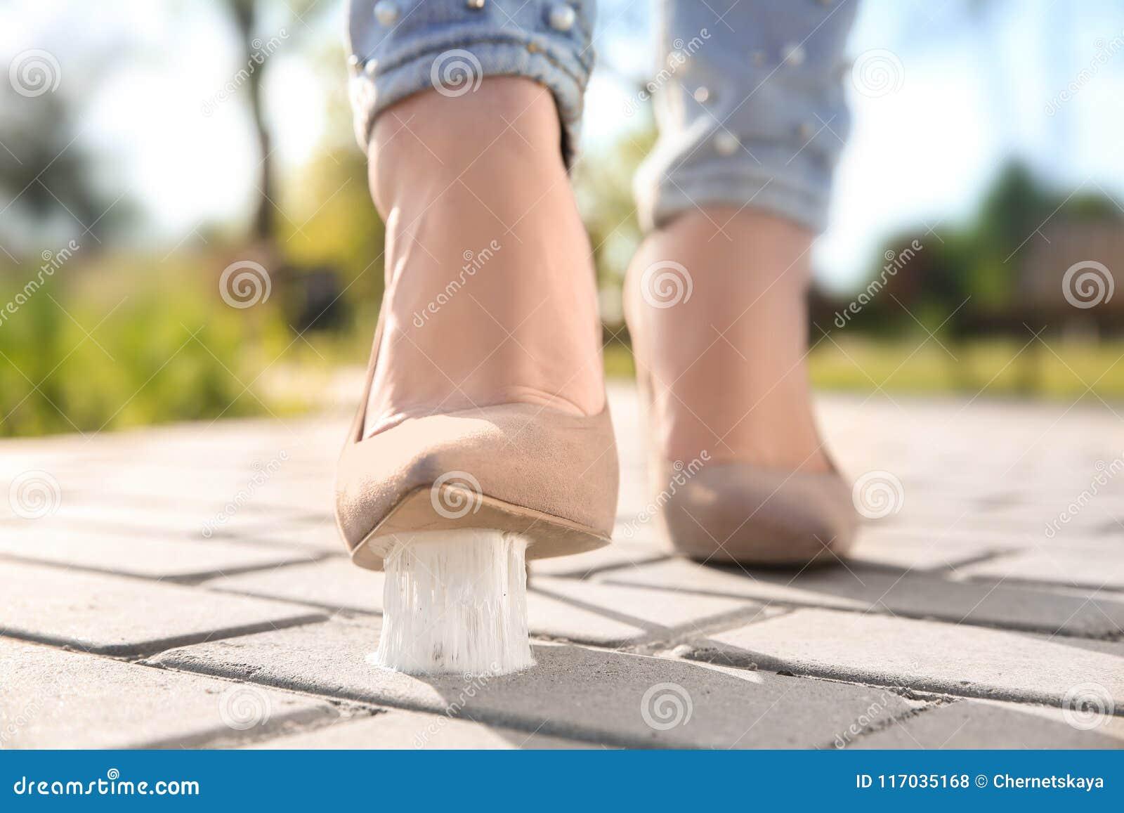 Vrouw die in kauwgom op stoep stappen