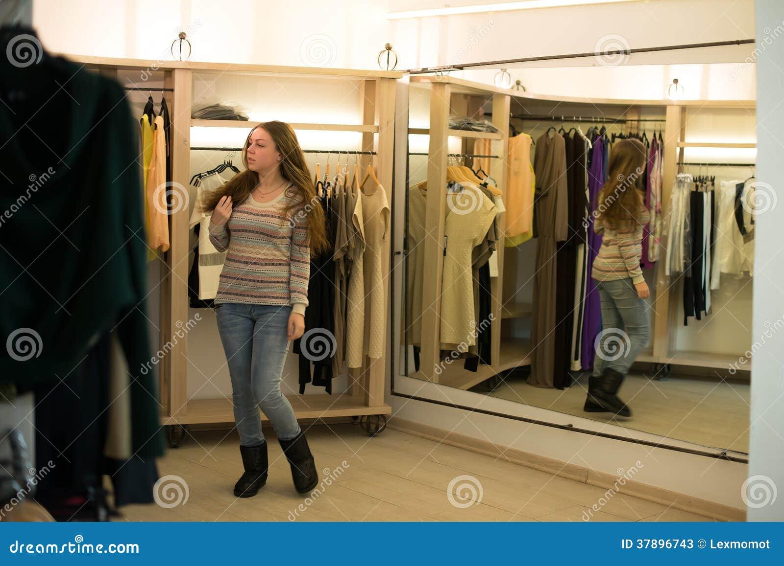 Vrouw die kiezend kleding die in onzekere spiegel kijken winkelen