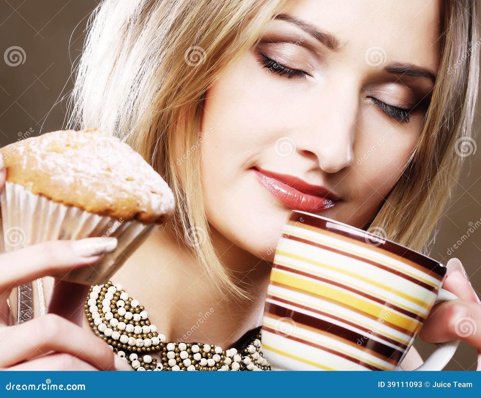 Vrouw die koekje eten en koffie drinken.