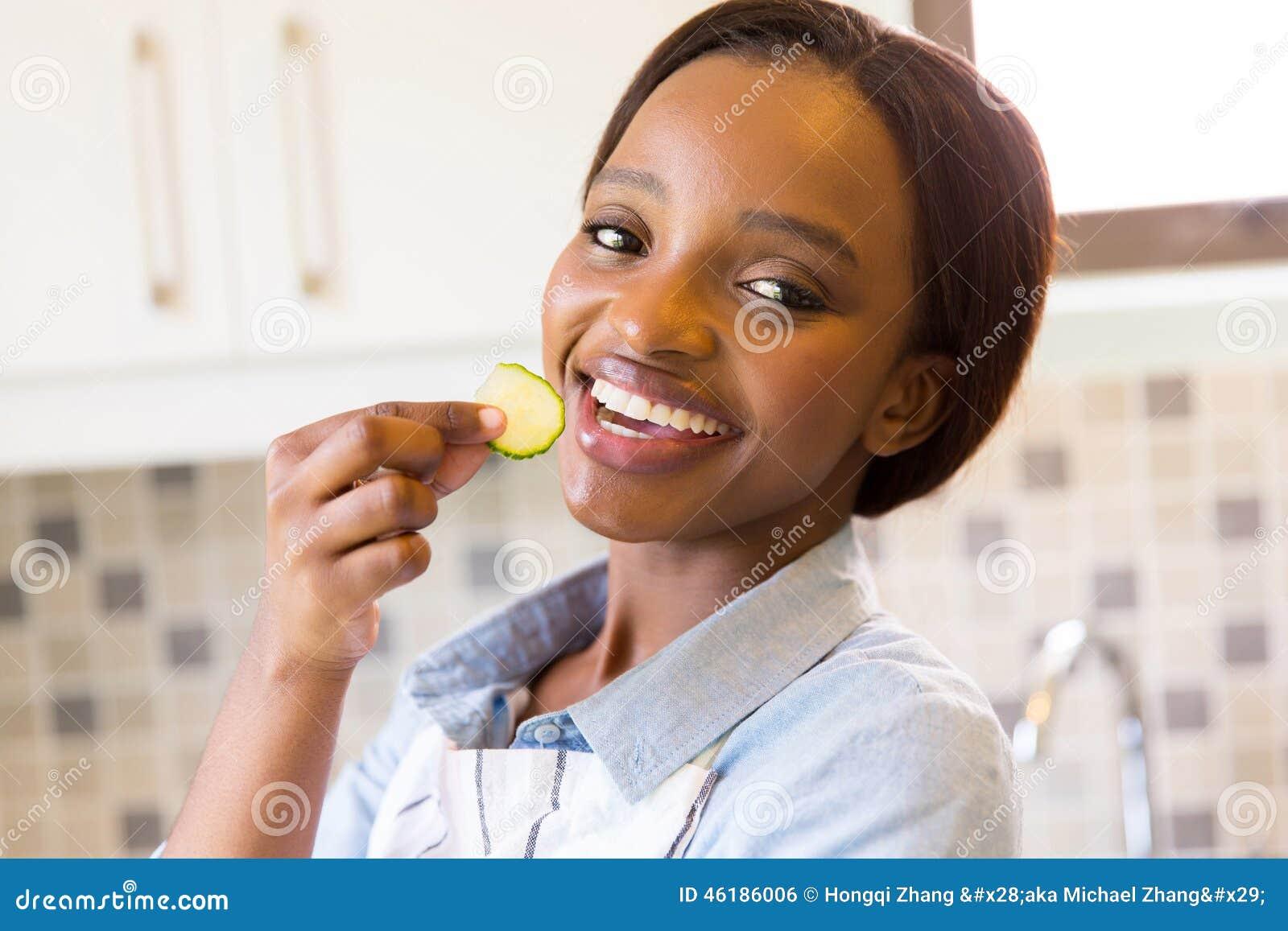 Vrouw die komkommer eet