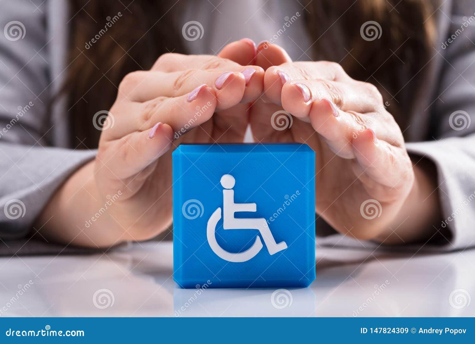 Vrouw die Kubiek Blok met Gehandicapt Handicappictogram beschermen
