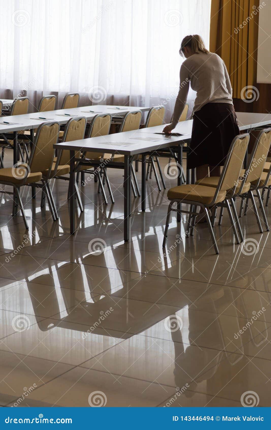 Vrouw die lijsten in conferentieruimte voorbereiden