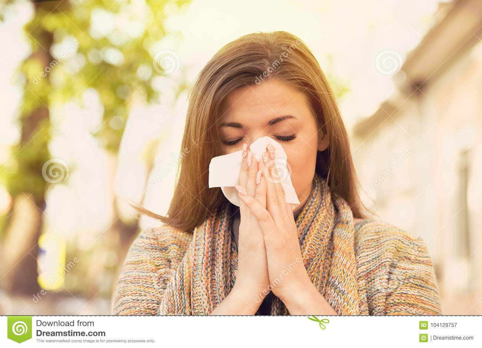 Vrouw die met allergiesymptomen neus blazen