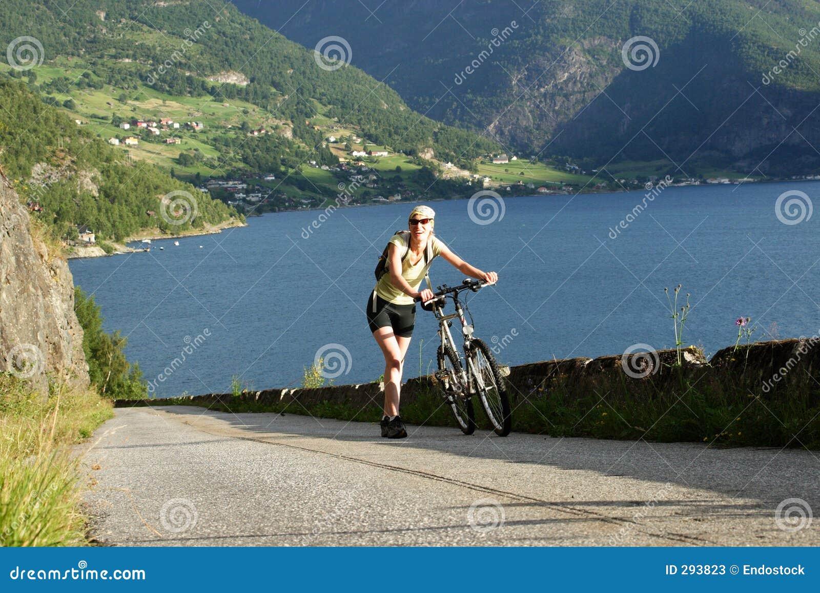 Vrouw die met fiets in de bergen loopt