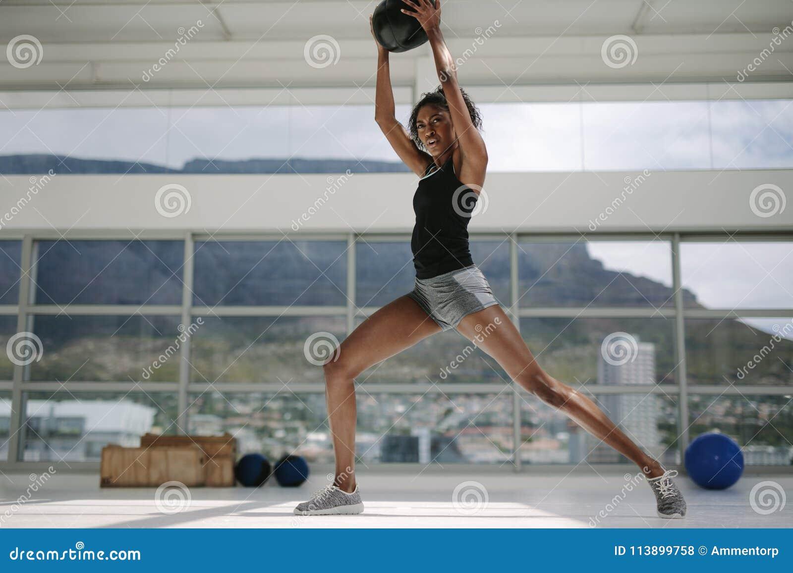 Vrouw die met geschiktheidsbal uitwerken