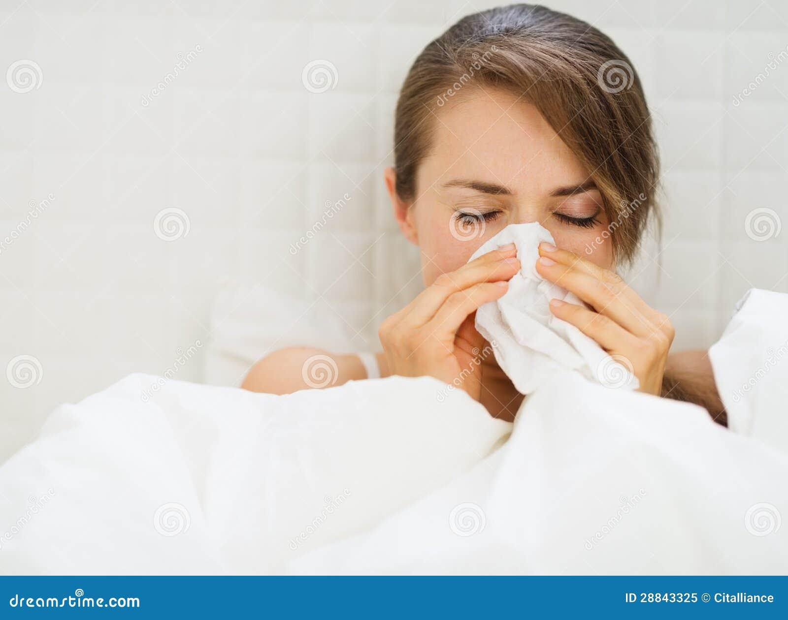Vrouw die met griep in bed leggen