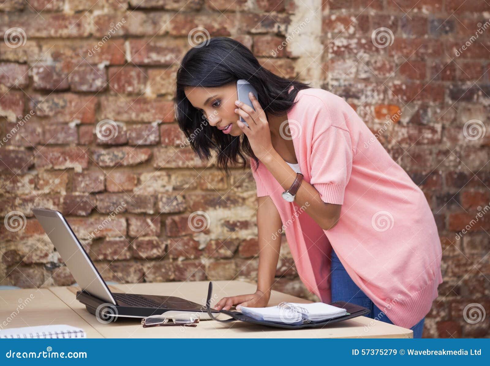 Vrouw die met haar mobiele telefoon roepen en agenda bekijken