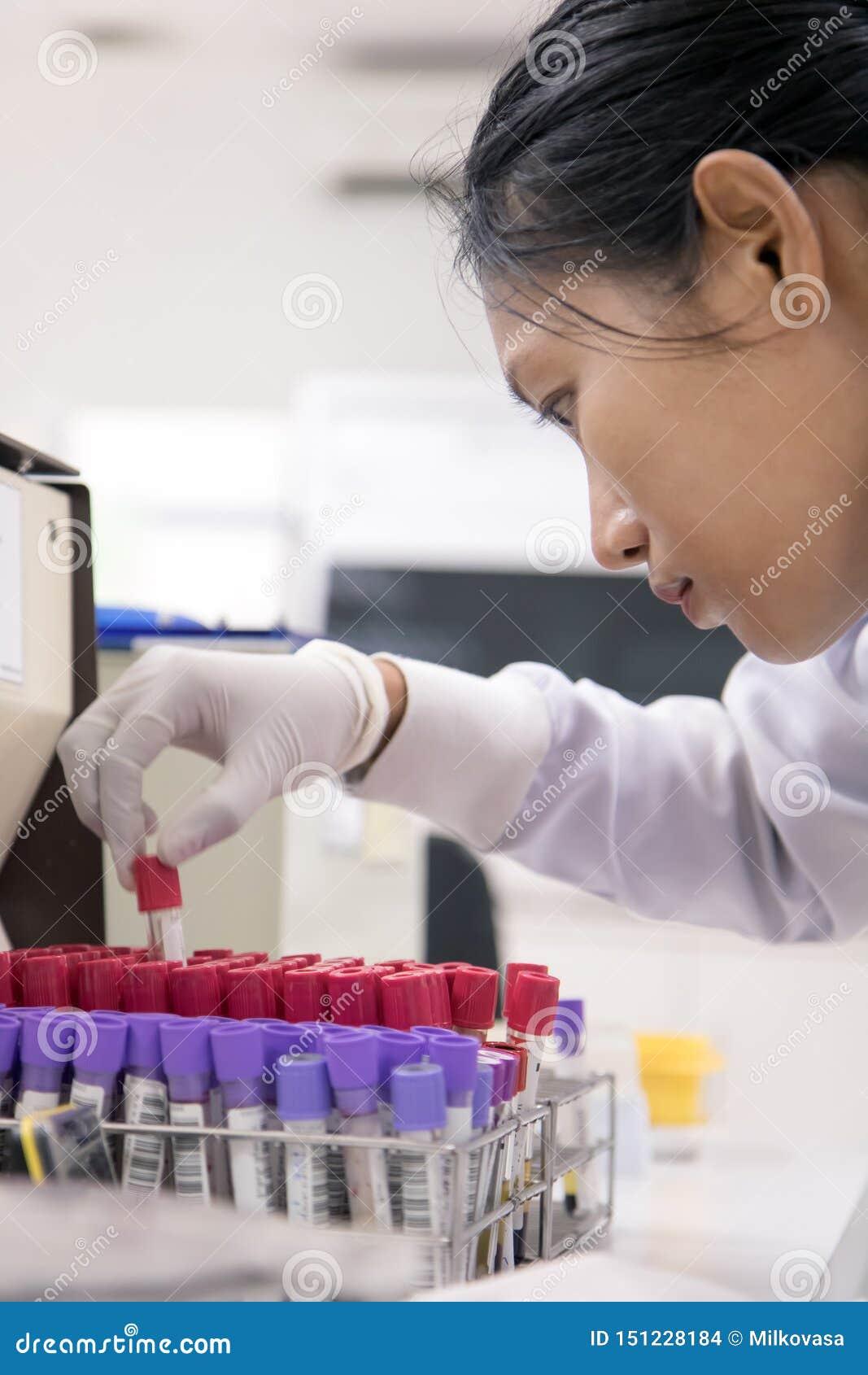 Vrouw die met het testen van buizen bloed werken