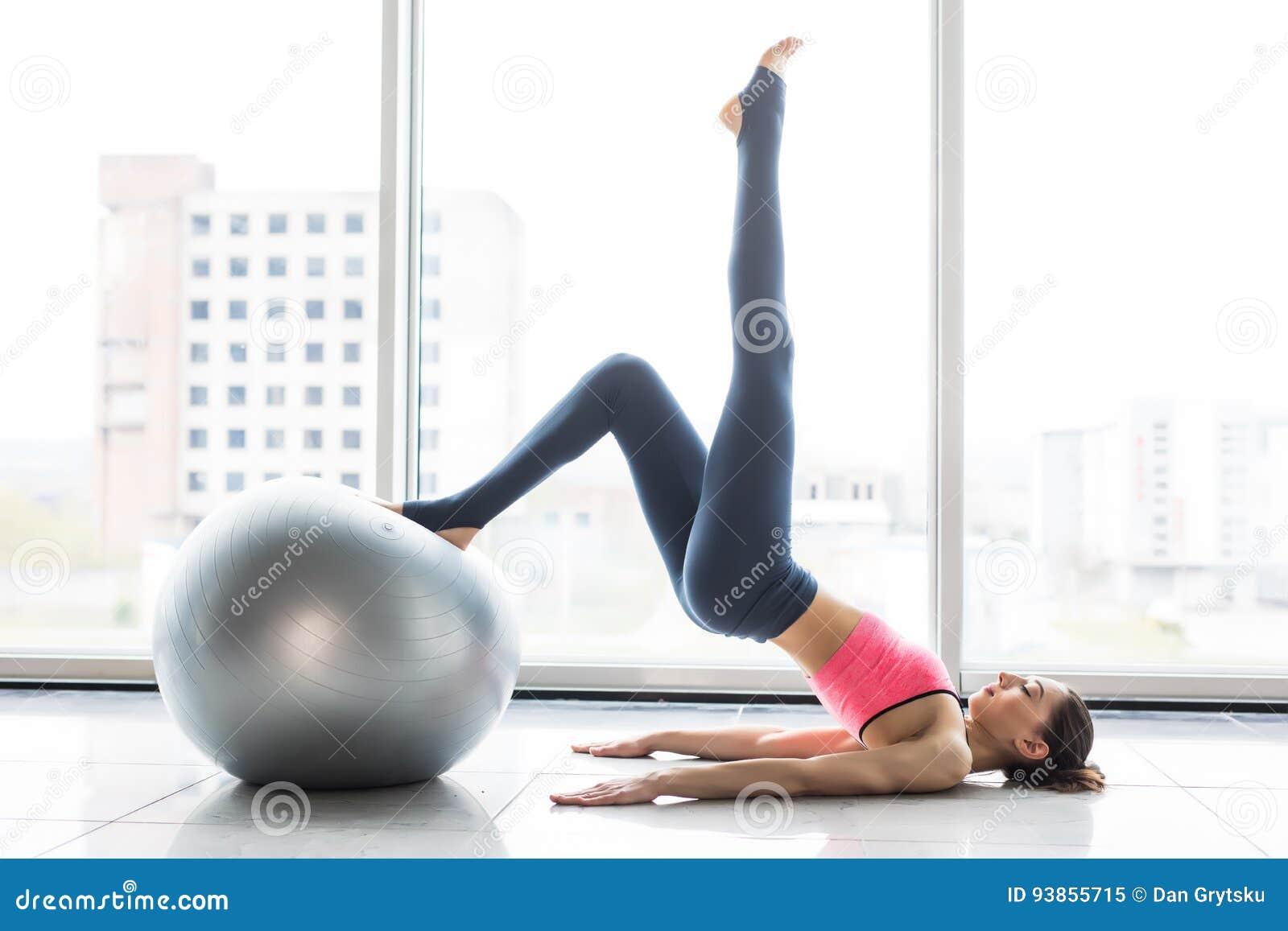 Vrouw die met oefeningsbal uitwerken in gymnastiek Pilatesvrouw die oefeningen in de ruimte van de gymnastiektraining met geschik
