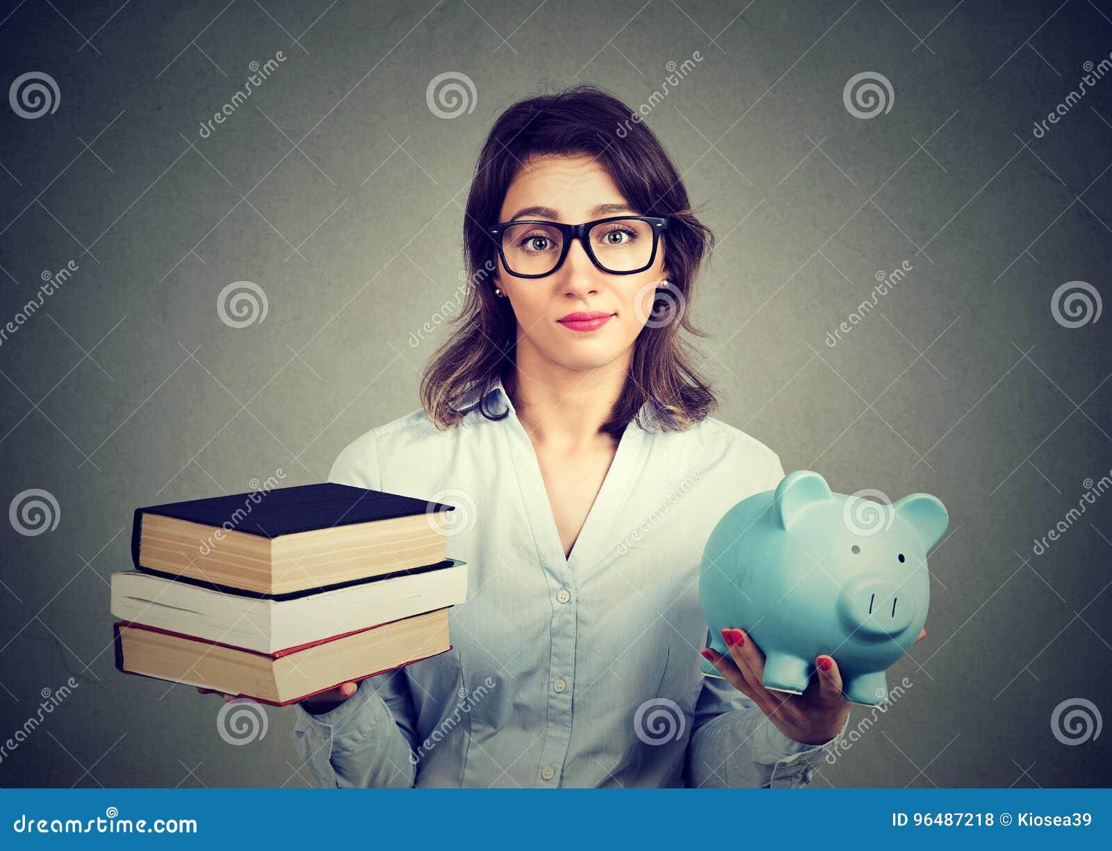 Vrouw die met stapel boeken en het hoogtepunt van het spaarvarken van schuld carrièreweg heroverwegen