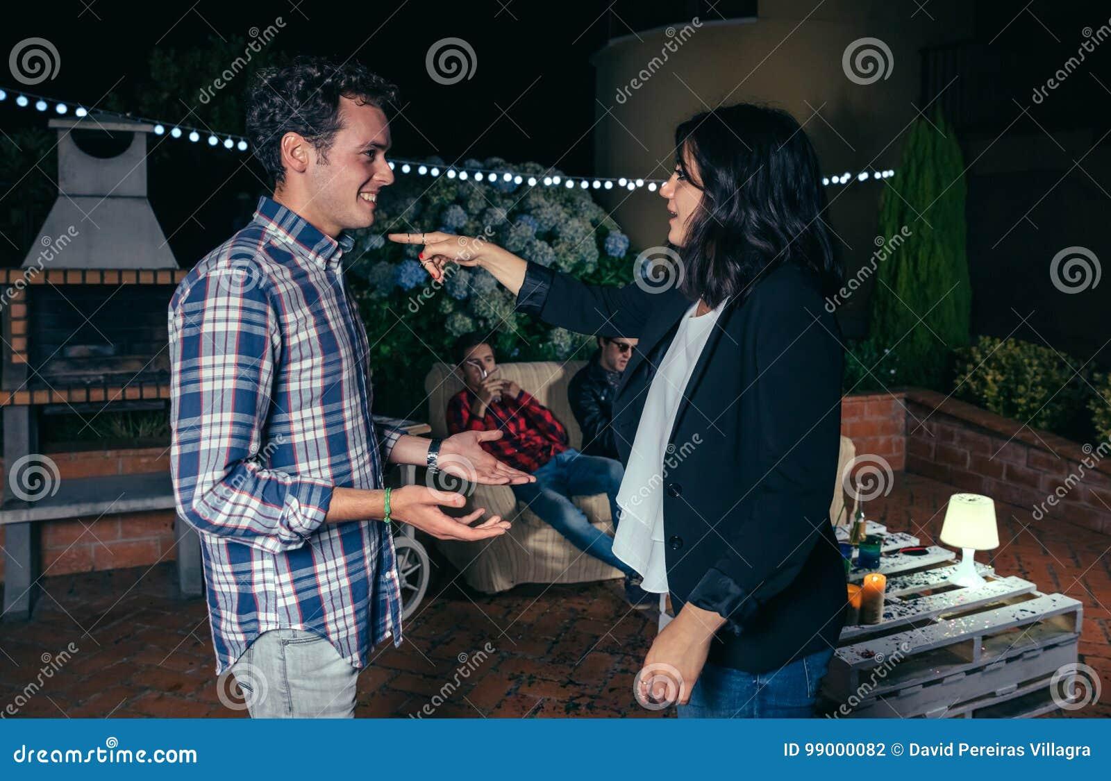Vrouw die met vinger aan de glimlachende mens in partij richten