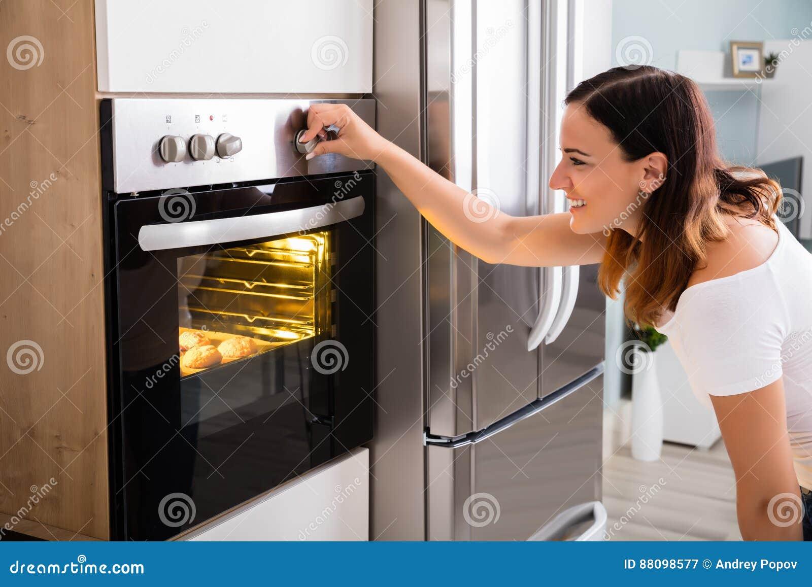 Vrouw die Microgolf Oven In Kitchen gebruiken