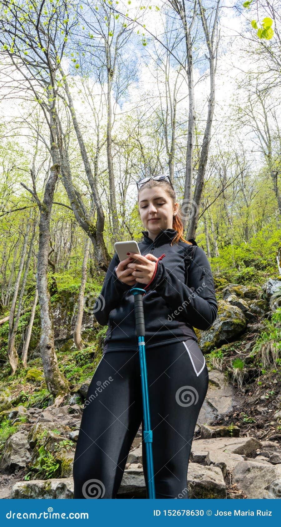 Vrouw die mobiele telefoon in het bos Gelukkige jonge meisje lopen in het bos en het gebruiken van haar moderne celtelefoon met b