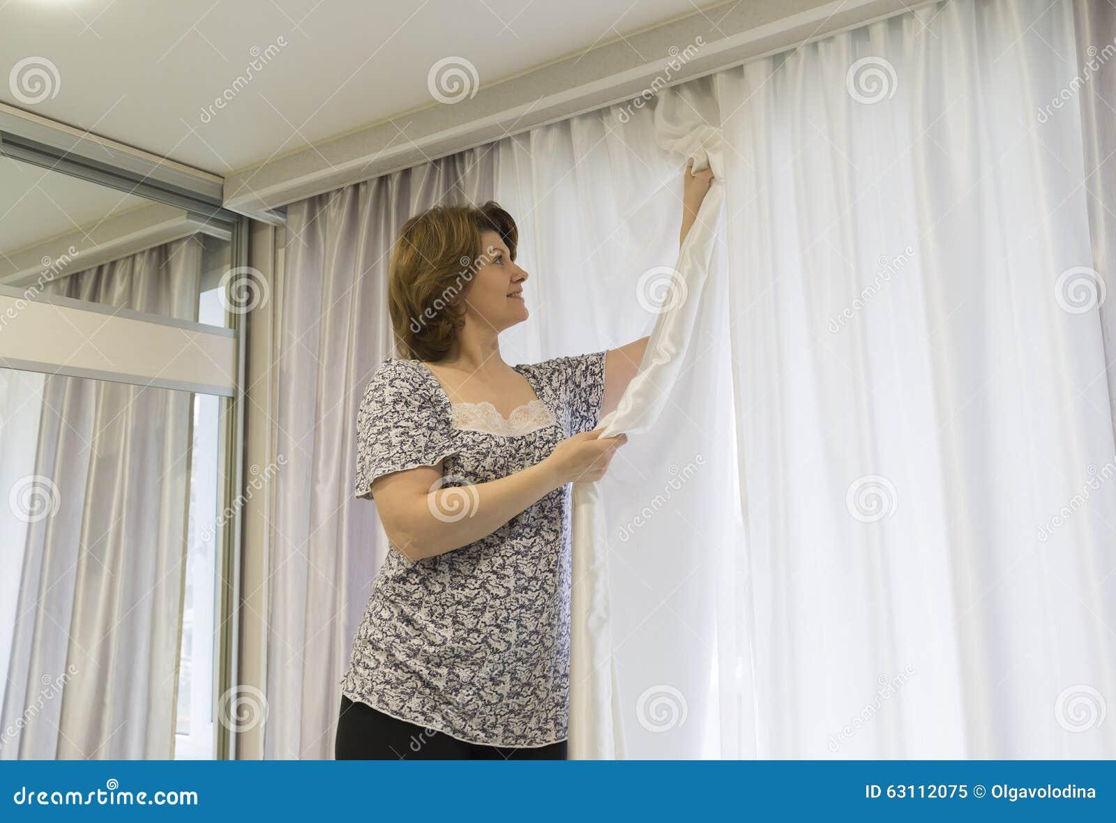 vrouw die omhoog zijn gordijnen hangen bij venster