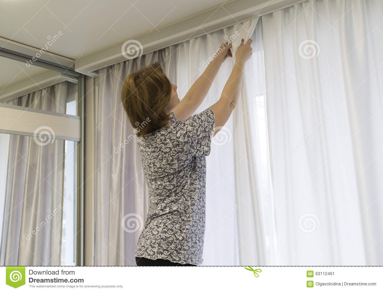 https://thumbs.dreamstime.com/z/vrouw-die-omhoog-zijn-gordijnen-hangen-bij-venster-63112461.jpg