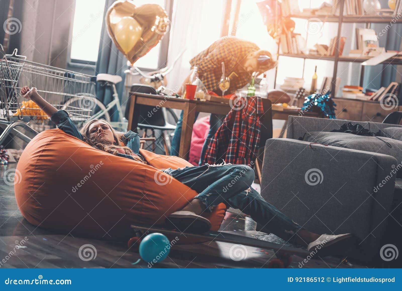 Vrouw die op beanbagstoel rusten terwijl man het schoonmaken erachter in slordige ruimte na partij