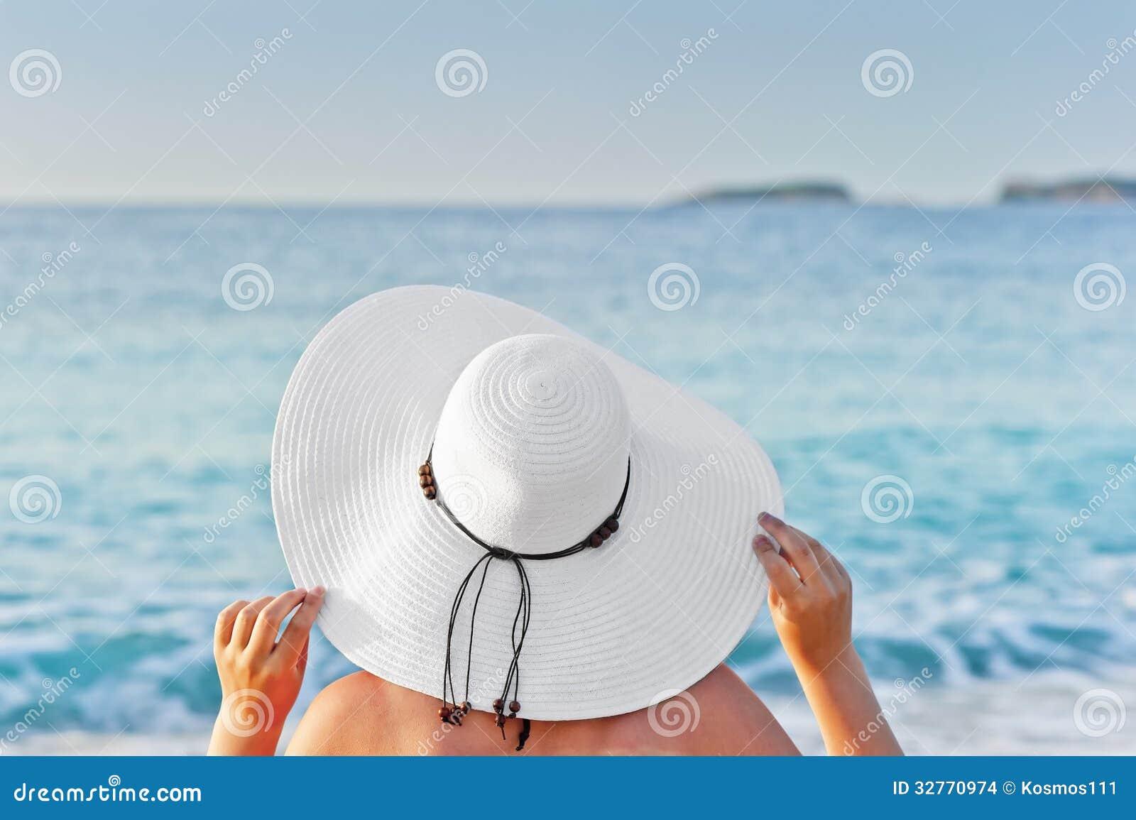 Vrouw die op een ligstoel op het strand zonnebaden en handenhoed houden