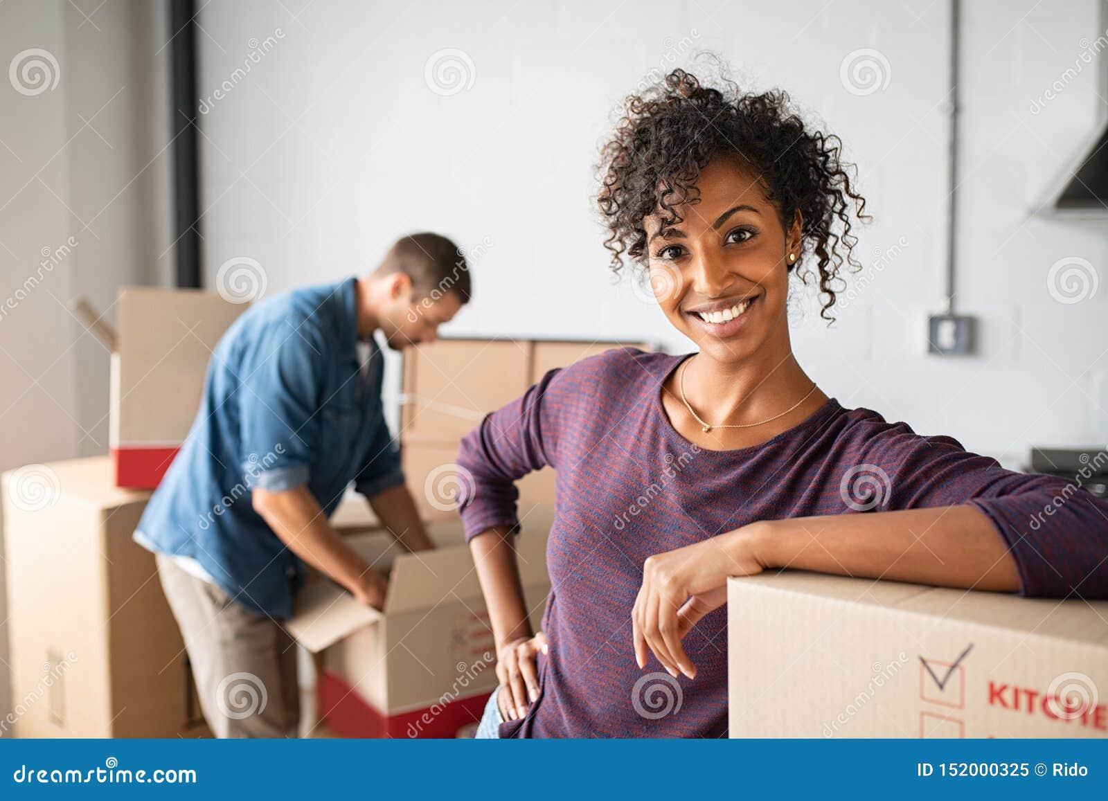 Vrouw die op kartondoos leunen terwijl het bewegen van huis