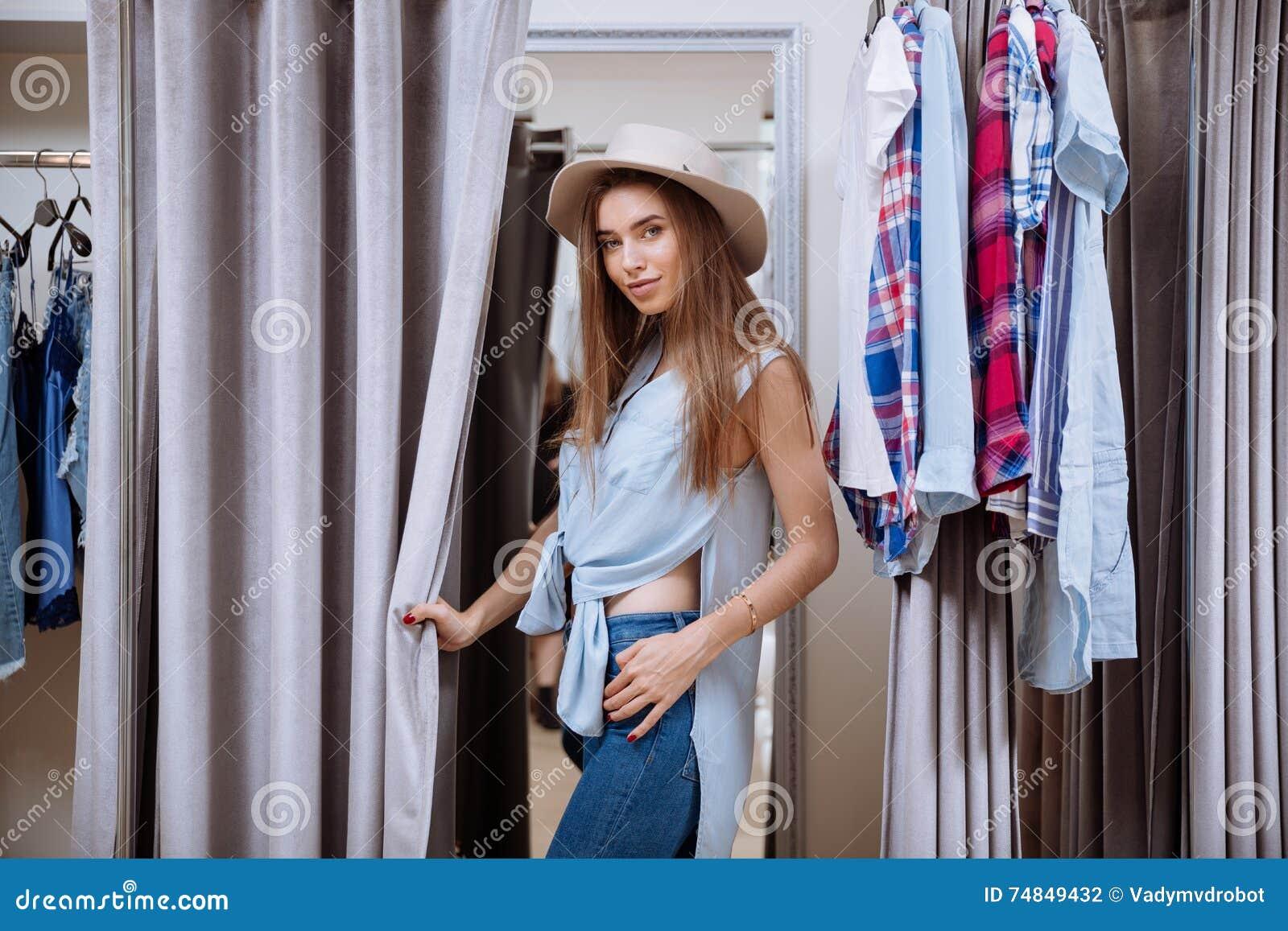 Vrouw die op kleren in montageruimte proberen van kledingswinkel