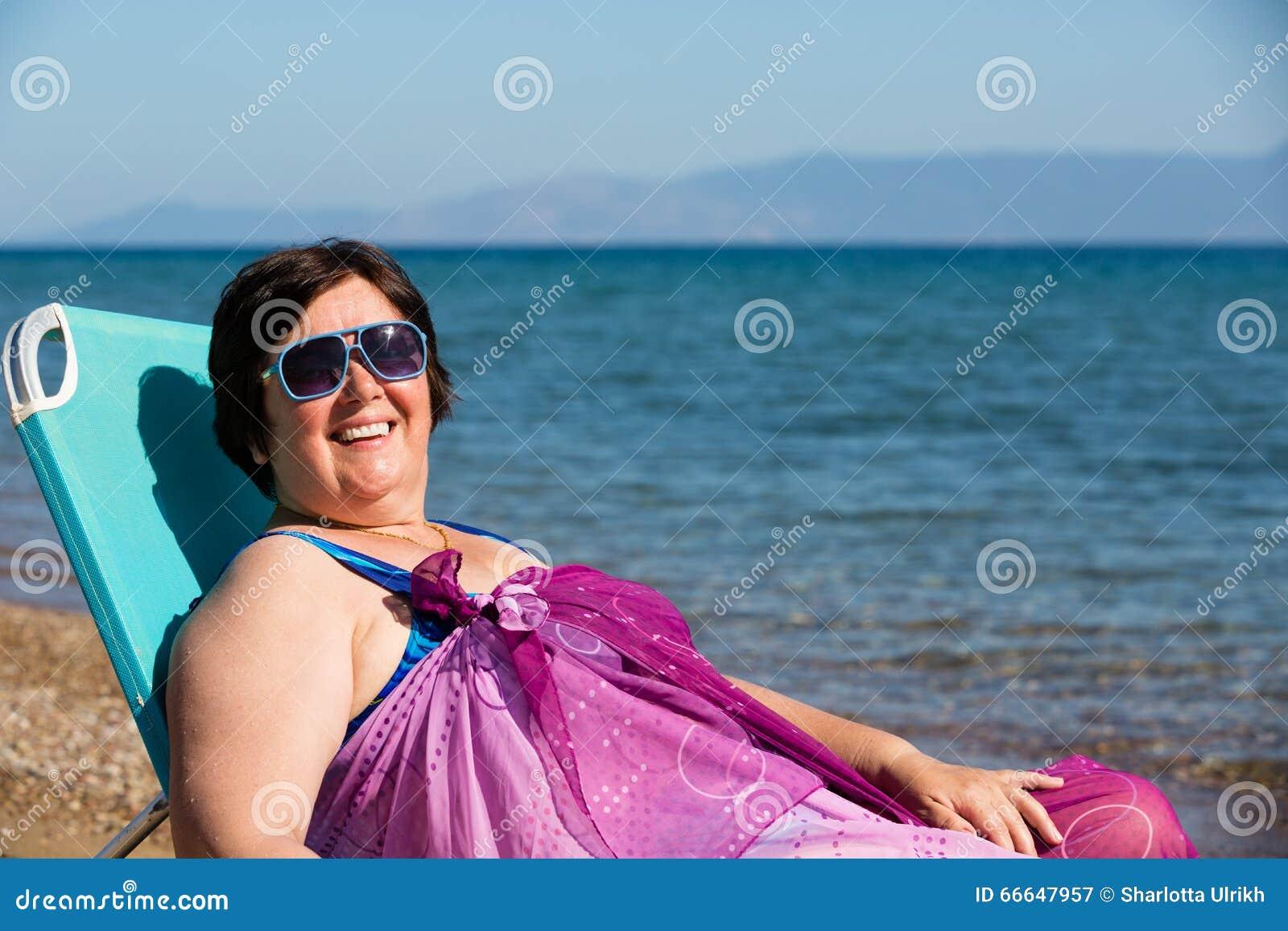 Vrouw die op middelbare leeftijd op het overzees rusten