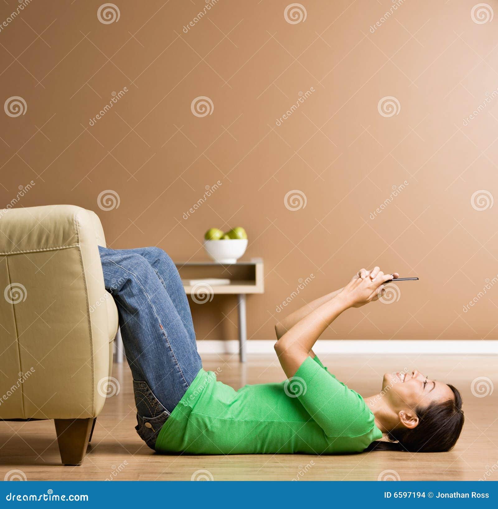 Vrouw die op vloer in het overseinen van de woonkamertekst legt