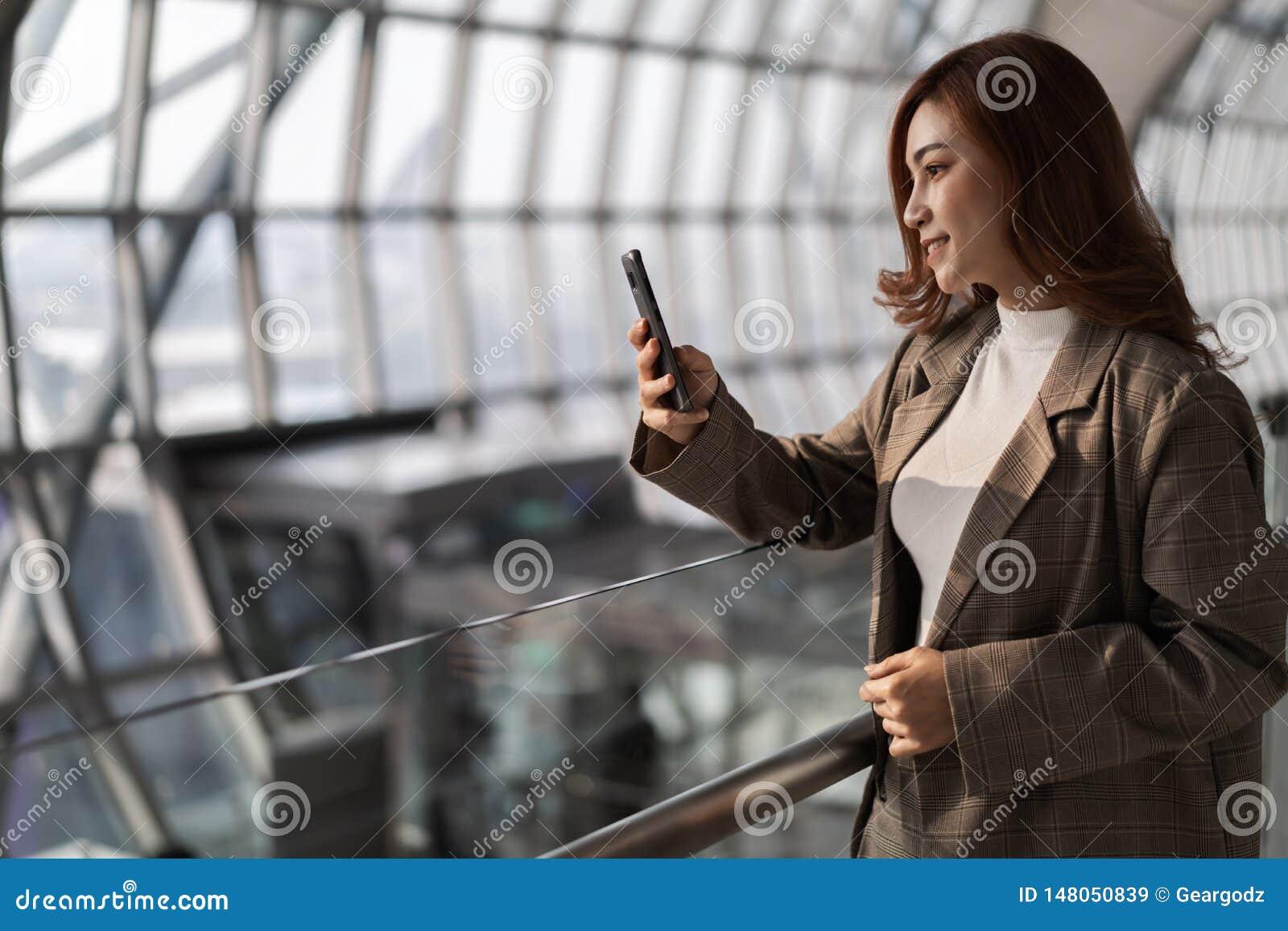 Vrouw die op vlucht wachten en smartphone in luchthaven met behulp van