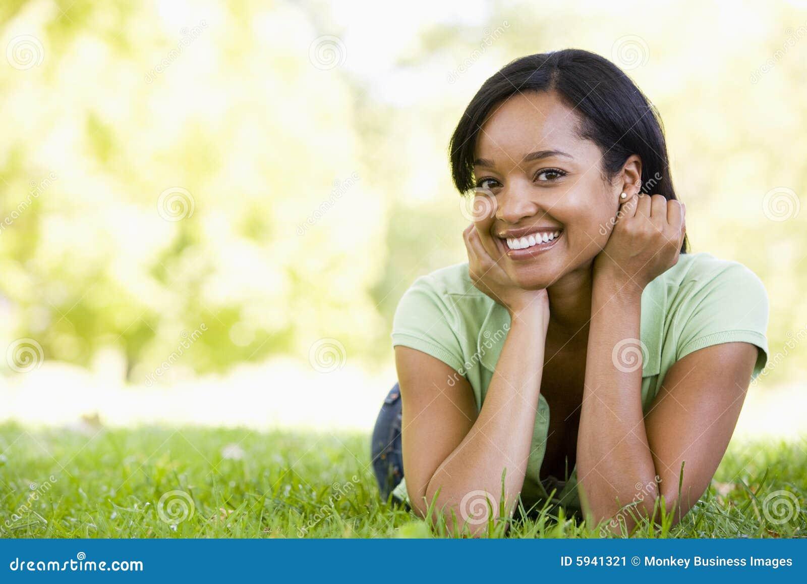 Vrouw die in openlucht glimlachend ligt