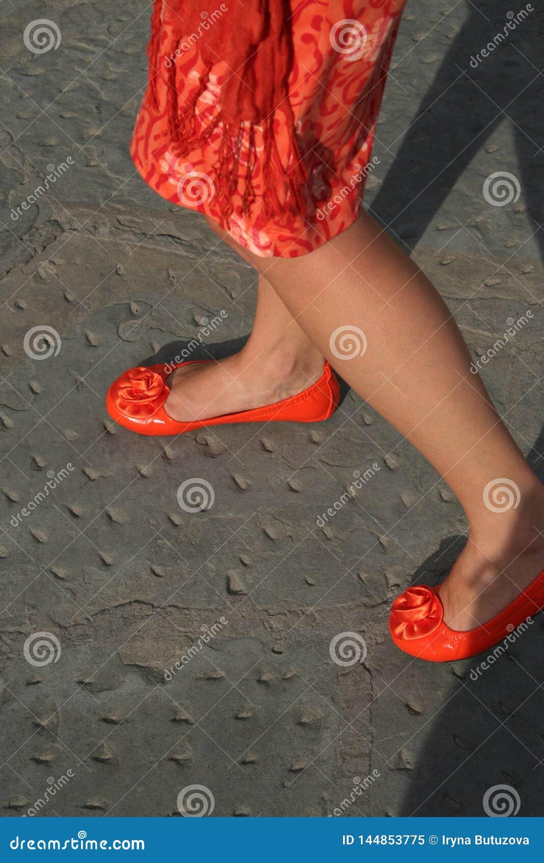 Vrouw die oranje kleding en heldere oranje schoenen dragen