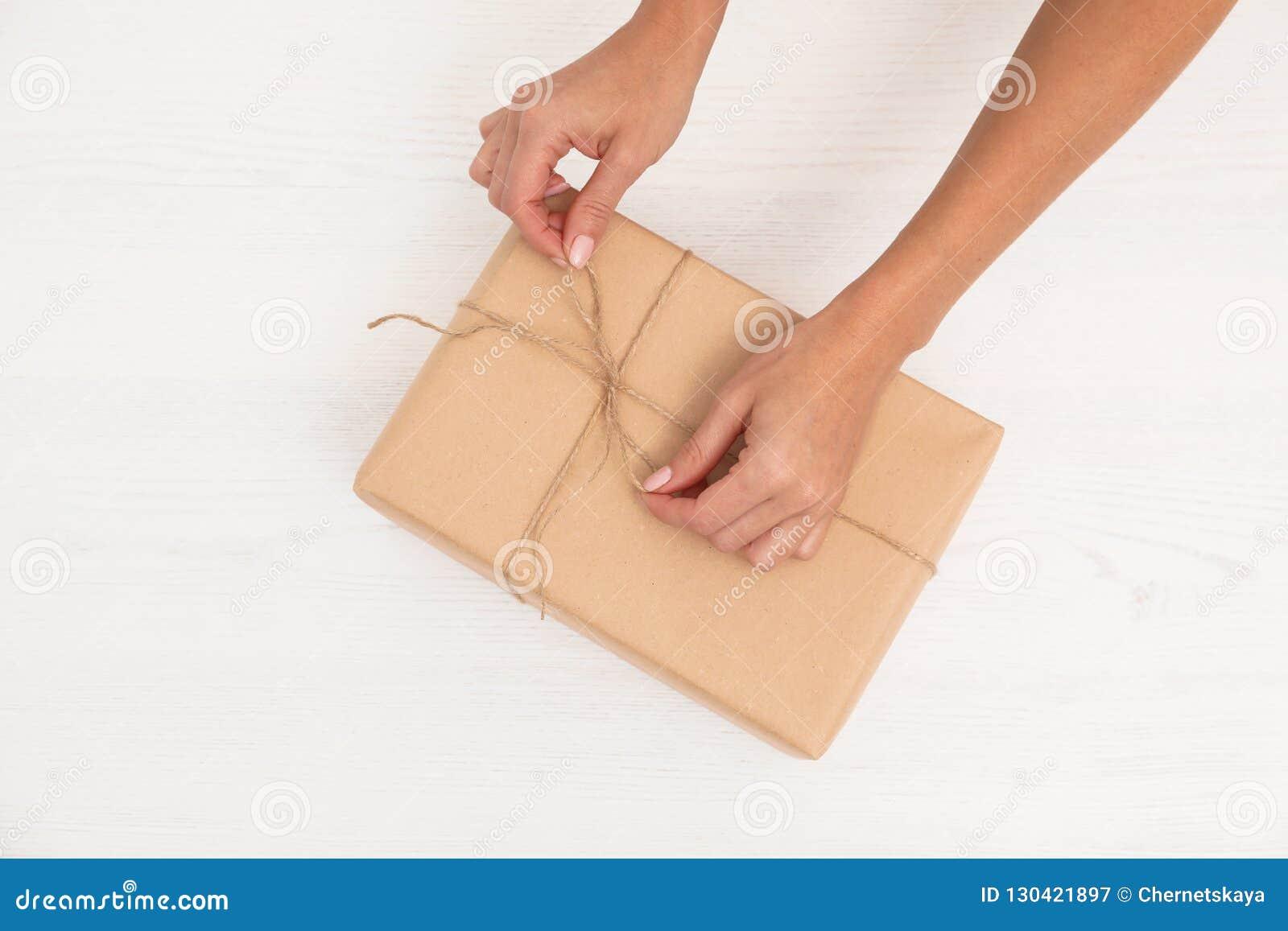 Vrouw die pakket met streng verfraaien