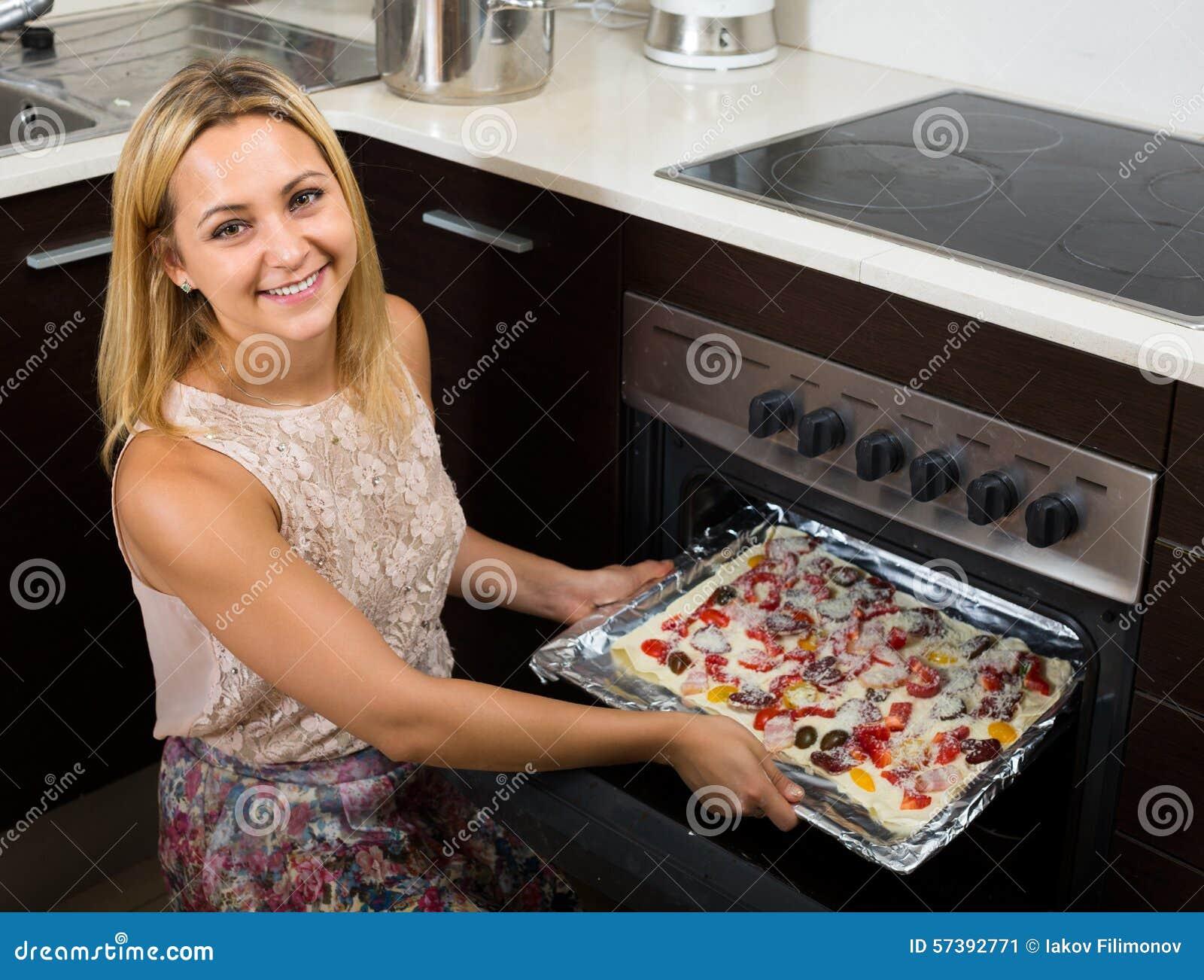 Vrouw die pizza in oven zetten