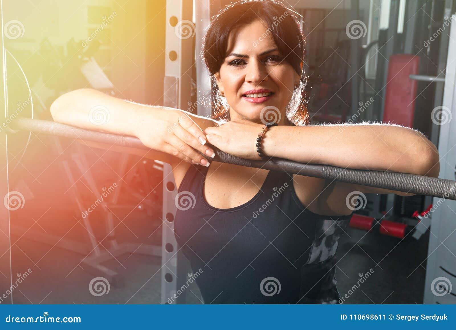 Vrouw die plus grootte in gymnastiek oefeningen met barbell doen powerlift, F