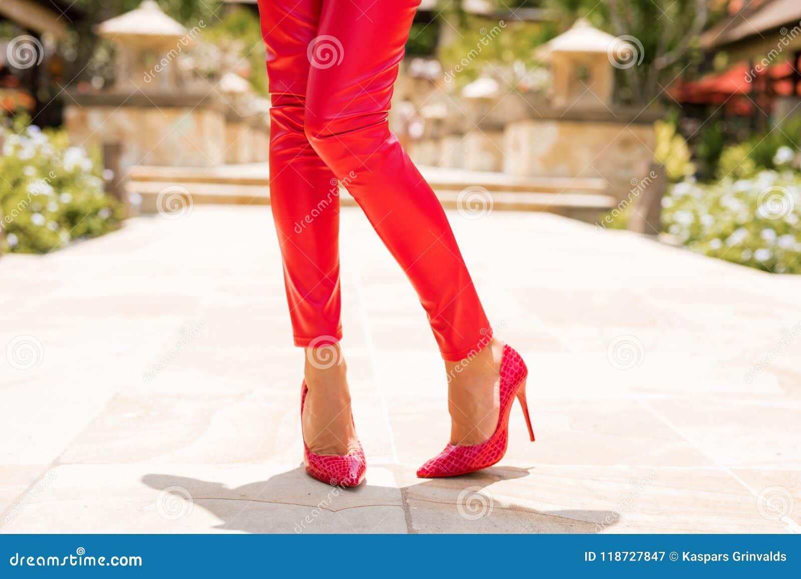 Vrouw die rode broek en hoge hielen dragen