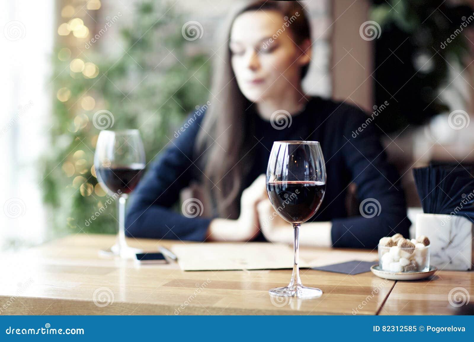 Vrouw die rode wijn in koffie drinken en rust hebben dichtbij venster