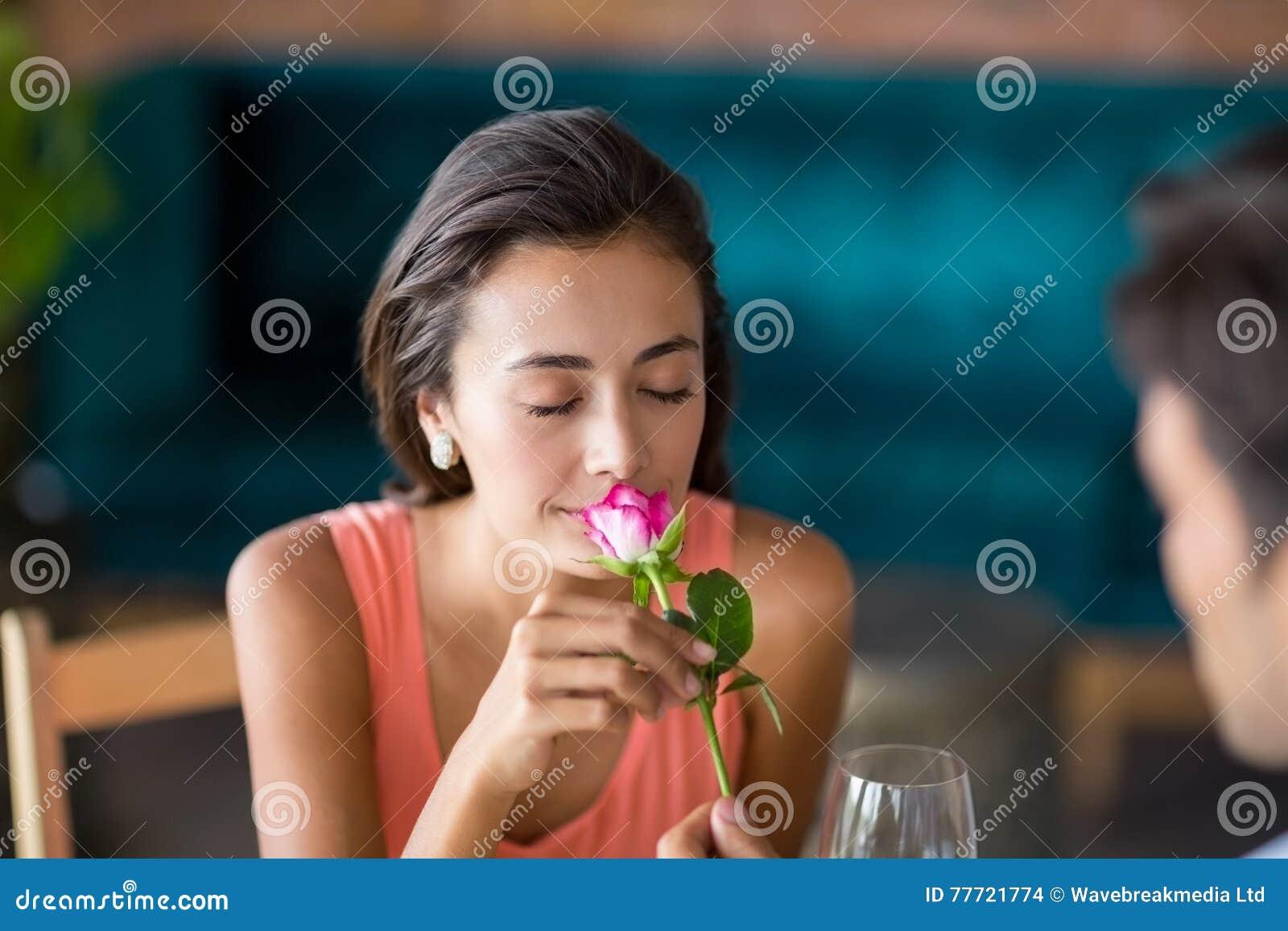 Vrouw die roze ruiken aangeboden door de mens