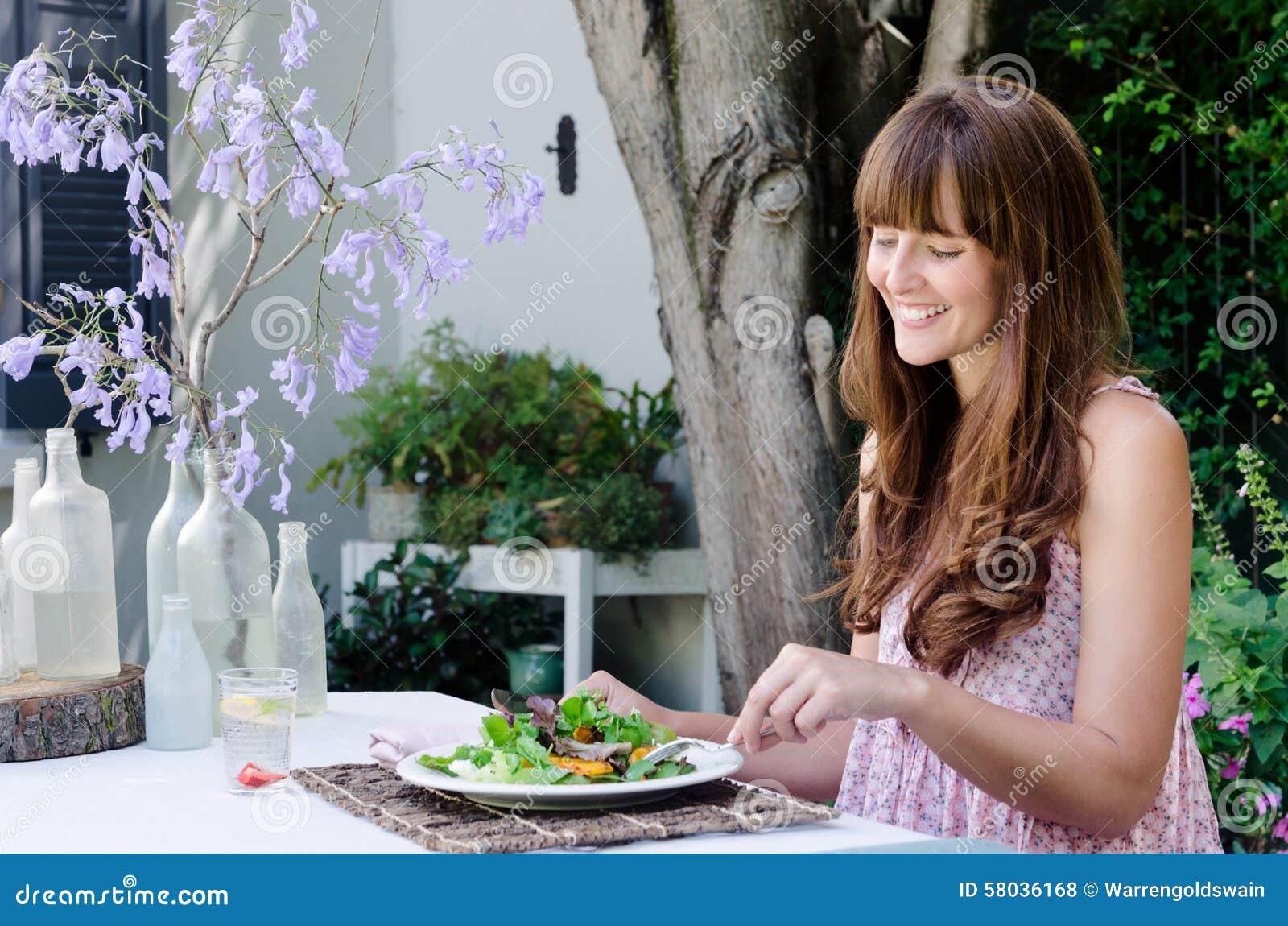 Vrouw die salade, dineren het in de open lucht eten