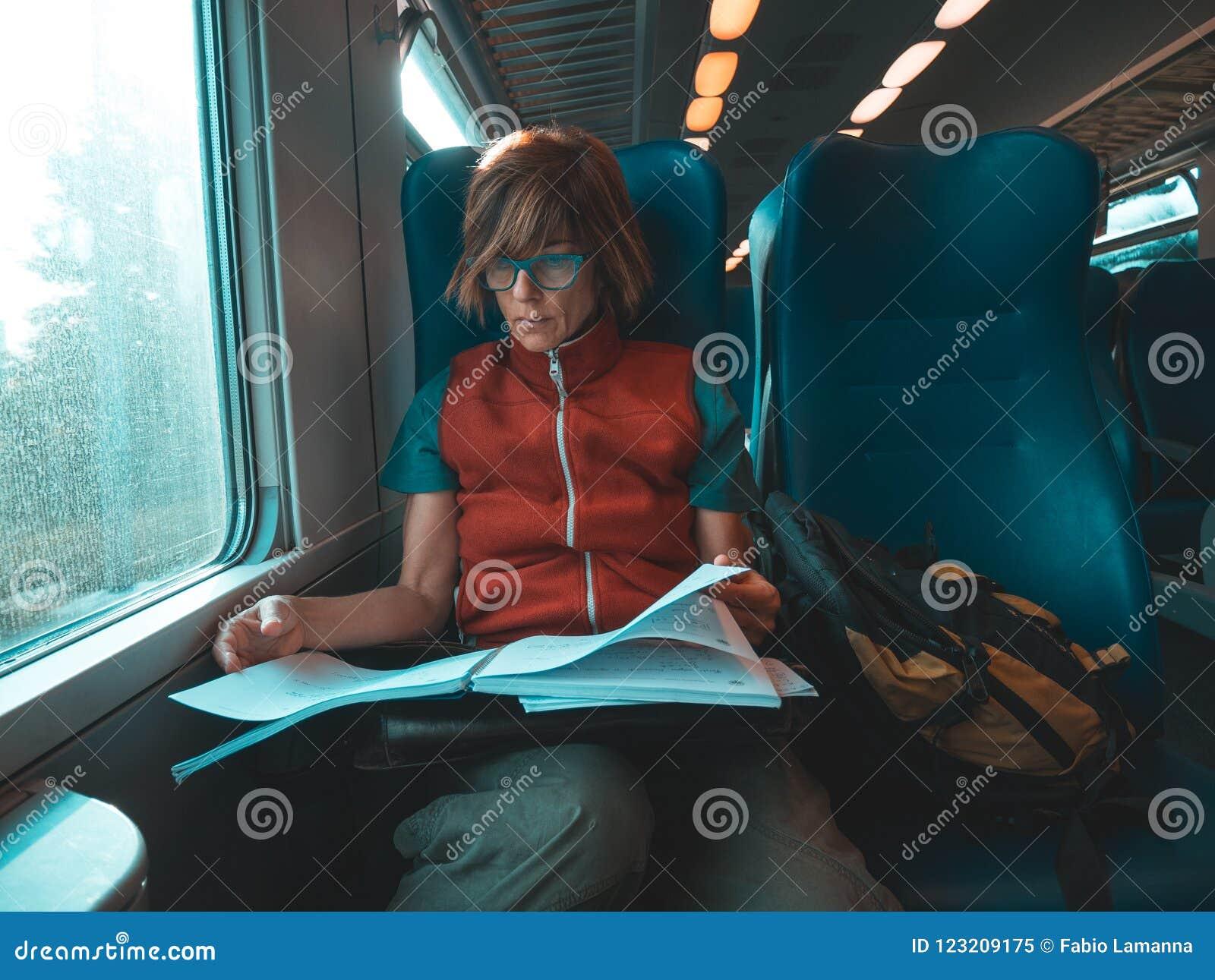 Vrouw die slimme telefoonzitting gebruiken die door treinhand reizen die op papier schrijven Het Desaturated koude toonkleur sort